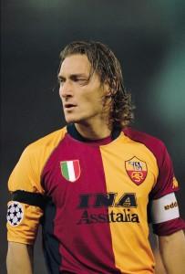Totti, ídolo da Roma, com a tradicional camisa amarela e vermelha. Escudo traz a loba capitolina.
