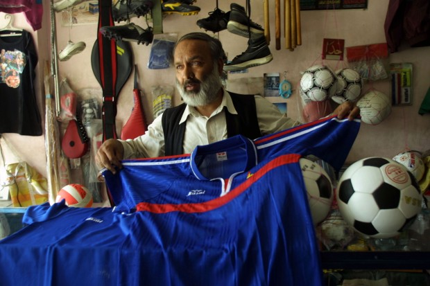 Afghan Shop Owner Shows Potential Customers A French Football Jersey
